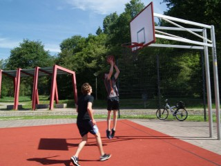 Boy goes for a layup in on on one streetball match